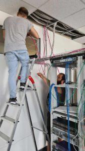 Bild von zwei Mitarbeitern beim Verlegen von Kabelanschlüssen